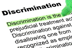 """Dictionary entry for of discrimination. Definition is """"Discrimination is the unjust or prejudicial treatment of different categories of people."""" Green highlighter is marking the definition."""
