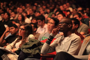 An auditorium of seated people look attentive, quiet, and ready to take notes on what they are observing.