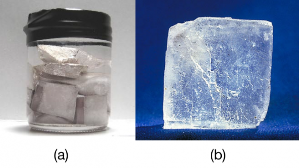"""a) Sodium metal is silvery, soft, and opaque and conducts electricity and heat well. (b) NaCl is transparent, hard, and colorless and does not conduct electricity or heat well in the solid state. These two substances illustrate the range of properties that solids can have. Source: """"Sodium"""" by Mrs Pugliano is licensed under the Creative Commons Attribution-ShareAlike 2.0 Generic; """"Halite(Salt)"""" is in the public domain;"""