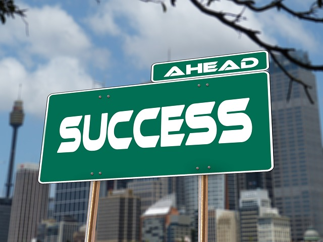 """Green and white road sign saying """"Success Ahead""""."""