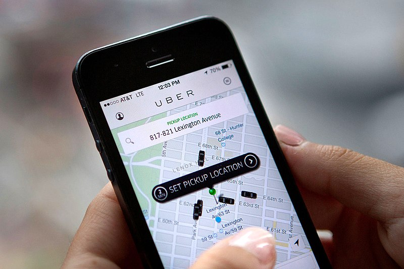 """Phone screen with Uber app open, showing a map of a city and several nearby Uber cars with a pin labeled """"Set pickup location."""""""