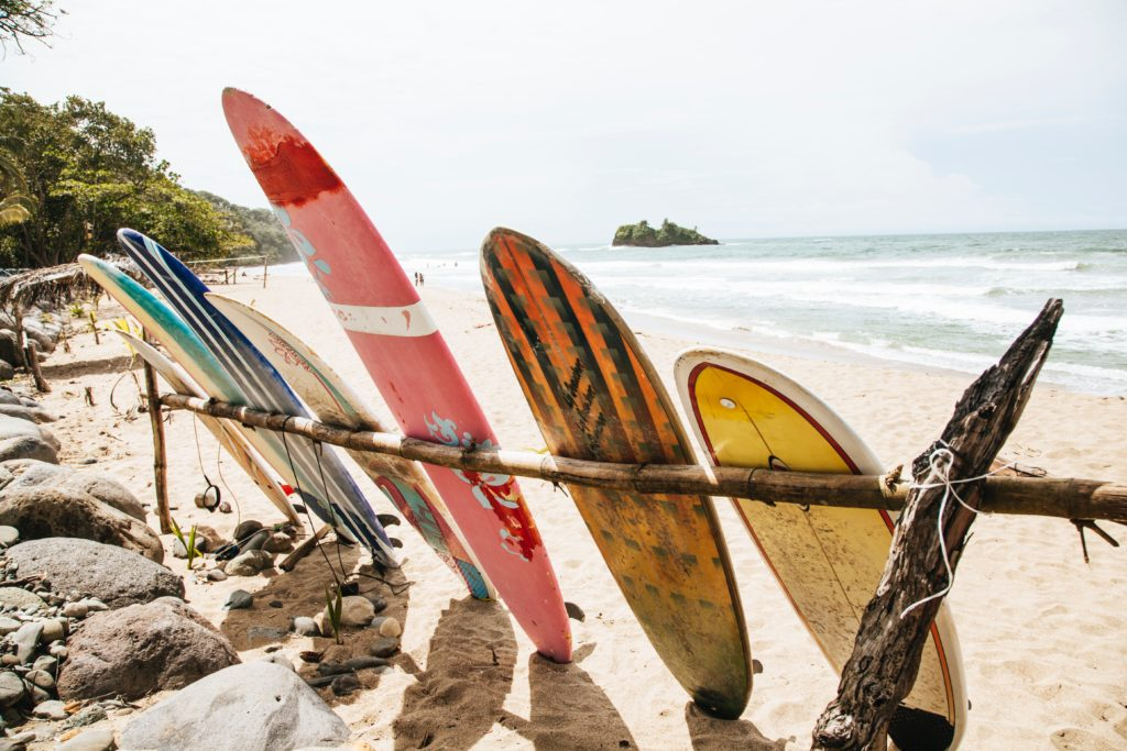 Photograph of seven surfboards leaning against a wooden fence on a beach.