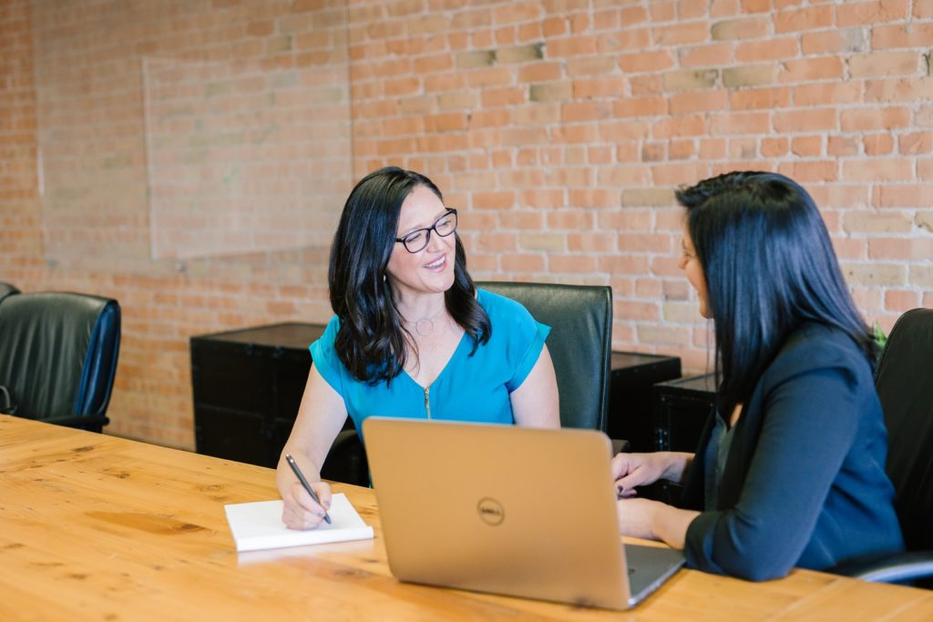Two women sit at a table in business clothes. One woman smiles and takes notes on a paper notepad while the other woman talks to her.