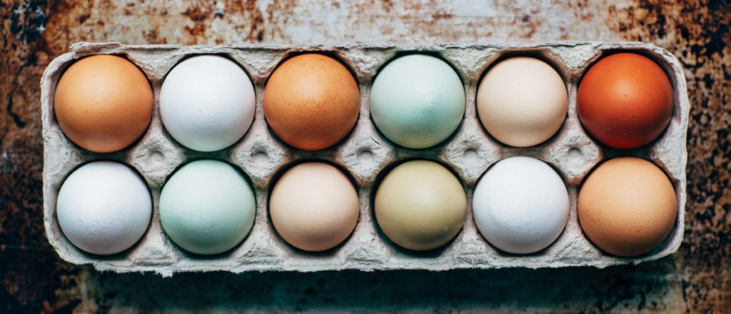 A carton of a dozen eggs in various shades of white and brown.
