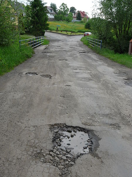 A one-land country road riddled with potholes.