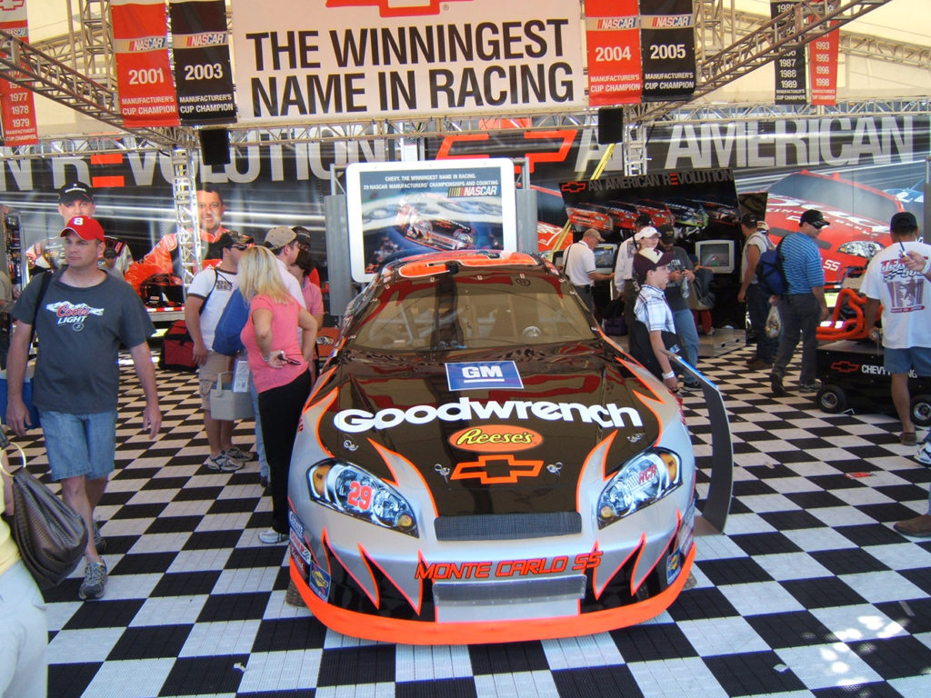 A group of people walking around a Nascar display area. There is a large Chevy racecar parked inside, covered in decals such as G M, Reese's candy, and Good wrench.