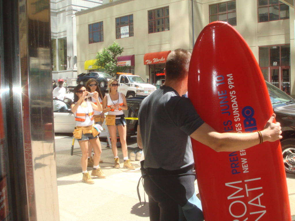 """Photograph of a man with a bright red surfboard with an ad for """"John from Cincinnati,"""" an HBO show. There are Women wearing safety vests in the background of the photo."""