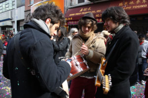 Three male hipsters play instruments on a street in Chinatown.
