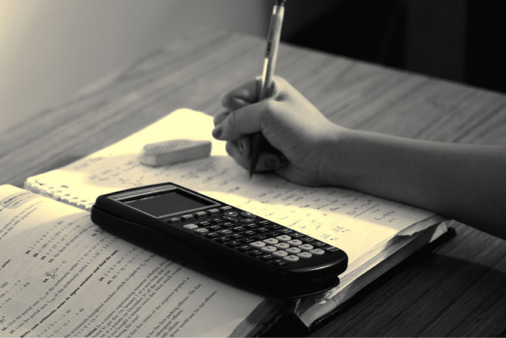 A photograph of a student's hand, working on a problem with an open textbook, a calculator, and an eraser.