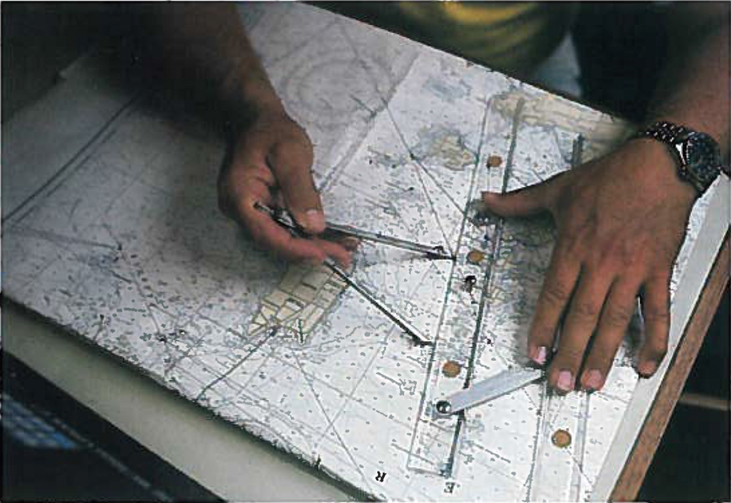 A photograph of someone measuring distance on a map using calipers and a ruler.