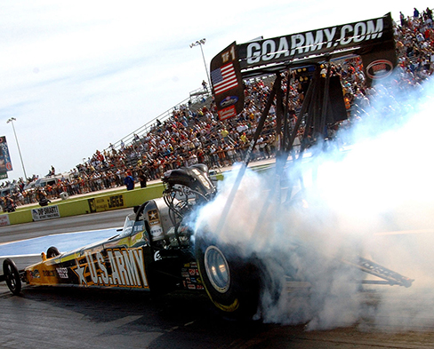 Picture shows a race car with smoke coming off of its back tires.