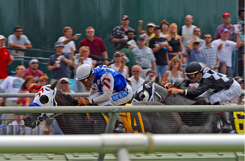 Picture shows two racehorses with riders accelerating out of the gate.