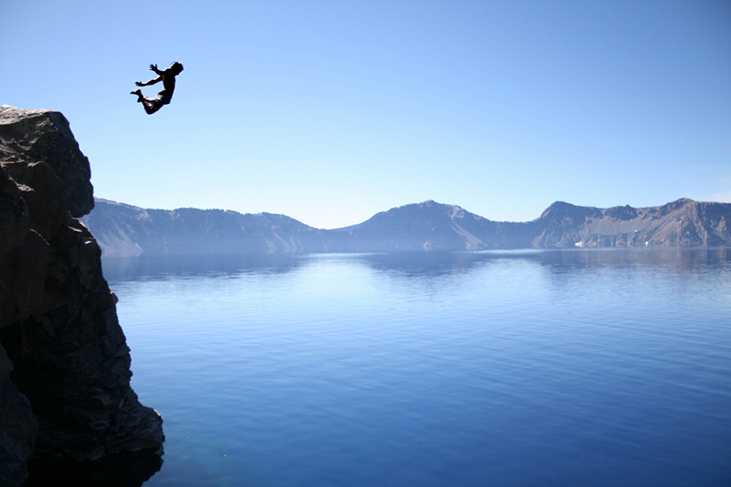 A photograph of a person jumping off a high cliff into a lake.