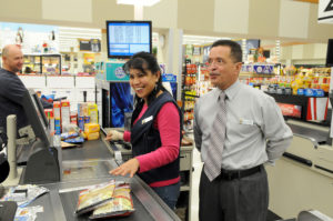 A female cashier in a grocery store checkout area is smiling while ringing up goods and talking with a man dressed in a tie standing behind her.