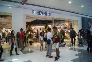 An image of the mall entrance to a Forever 21 store with lots of people walking around in front of the store.