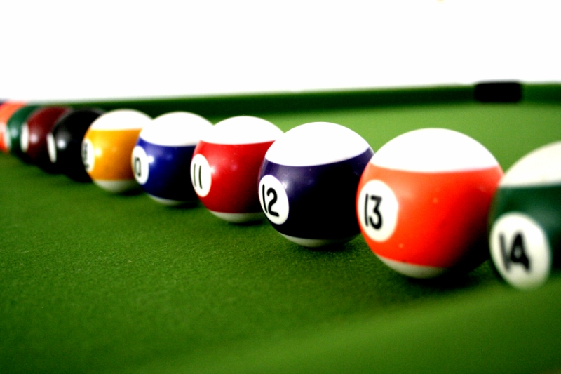 A row of striped pool balls on a green pool table with numbers facing forward (10, 11, 12, 13).