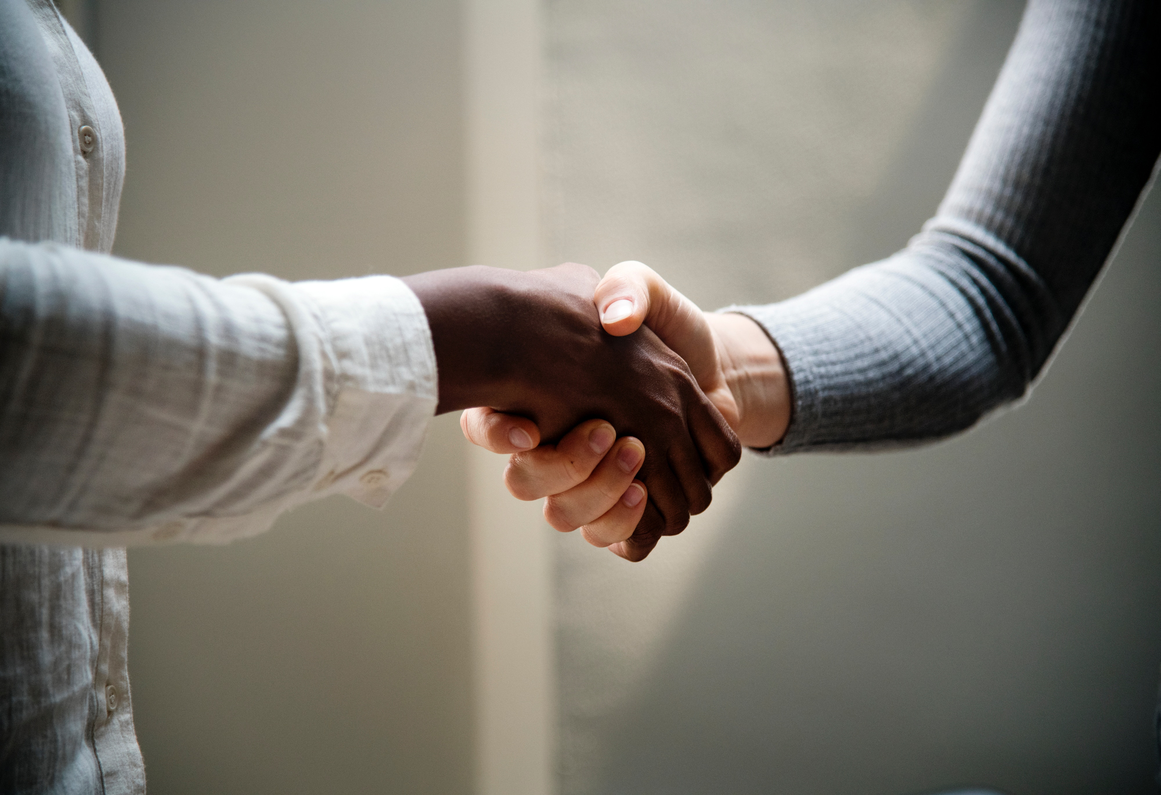 Photograph of two people shaking hands. Both individuals are only shown from hand to elbow.
