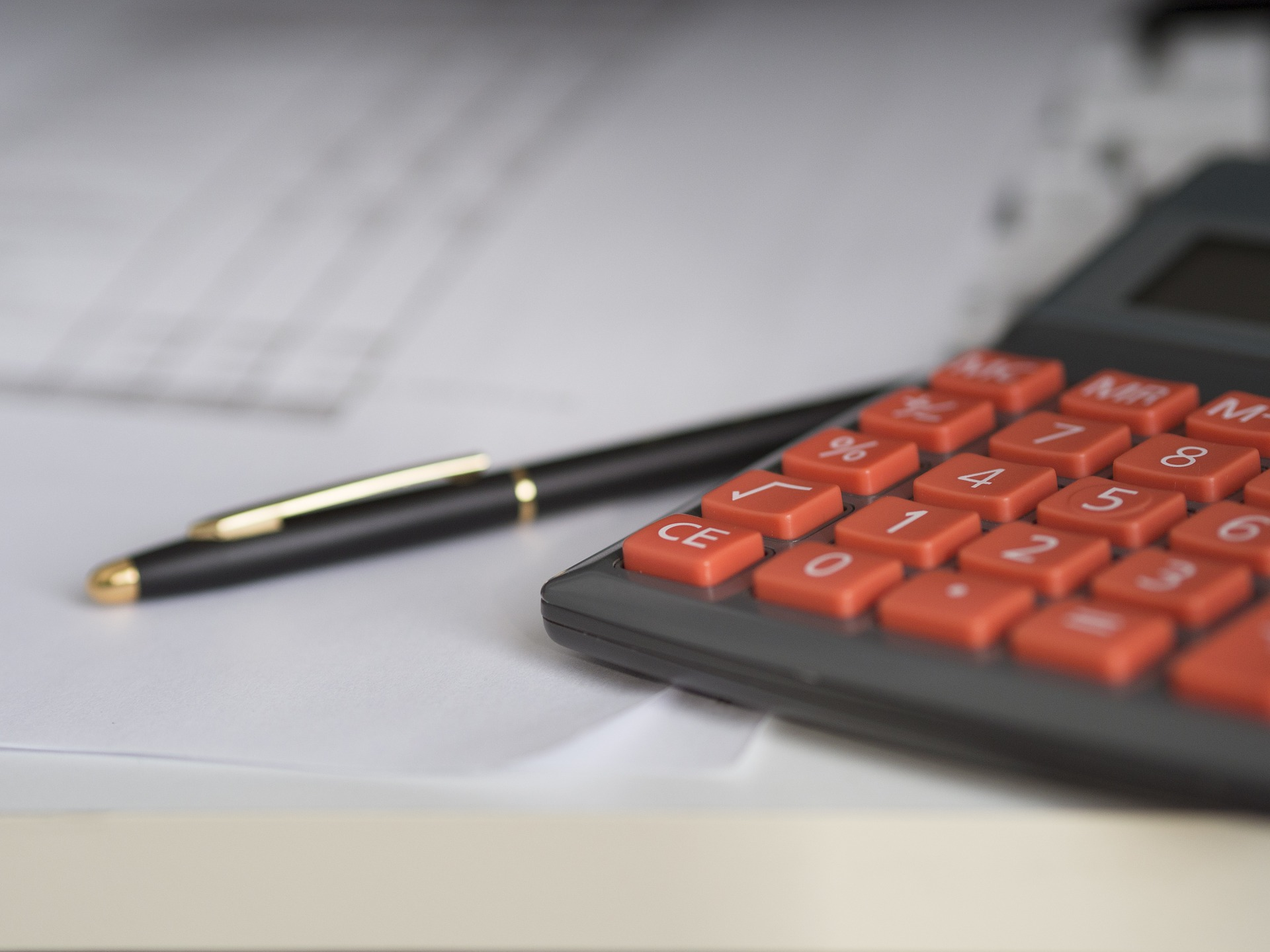 A calculator with red buttons on a paper with a pen