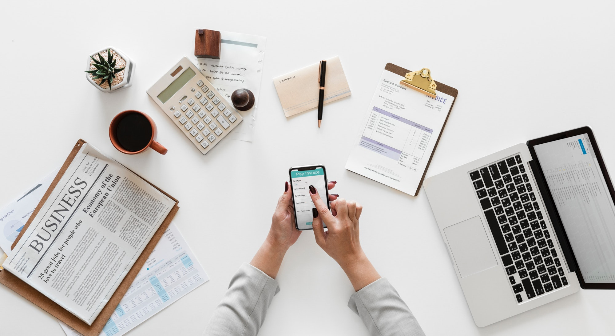 Various objects on a white desk. Objects include a laptop, clipboard, envelope, pen, calculator, mug, newspaper, and a person holding a phone.