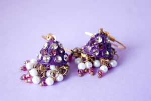 Image of two gold earrings made of tiny white, purple, and pink beads.