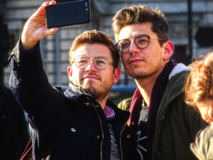 Two men dressed similarly, with the same haircut, and both wear round glasses take a selfie with each other.