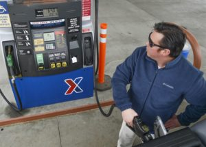 Man pumping gas into his car while looking at the display where the cost and gallons pumped are displayed.