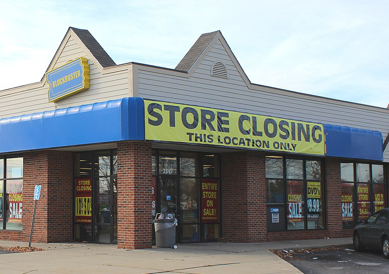 """Front of a Blockbuster store with large sign saying """"Store Closing""""."""