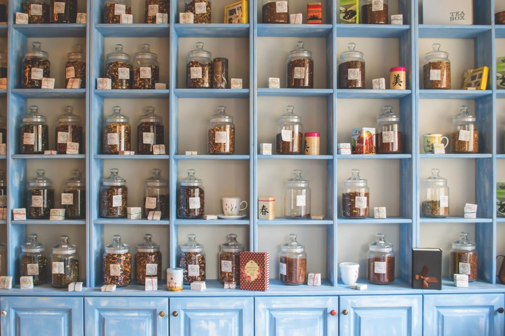 A blue shelf stocked with a variety of jarred spices