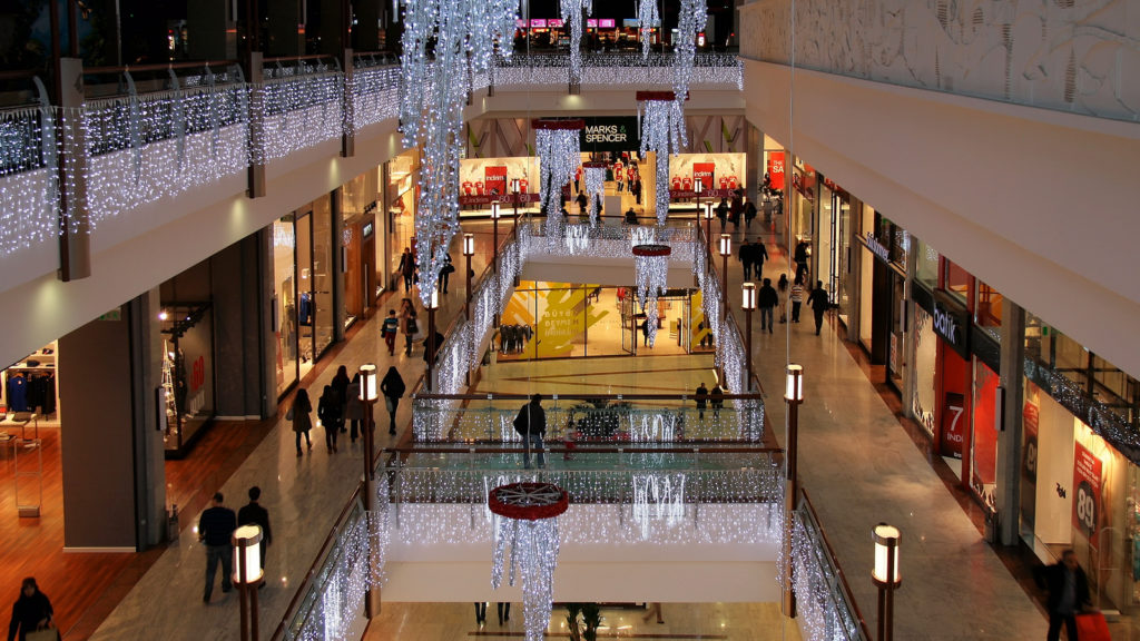 Photograph of a shopping mall. The photograph is taken from the third floor of the mall, and the second and first floor can be seen, as the center of the mall is open and bridged with walk ways. The mall is decorated for winter, and lights hang from the balconies of the third and second floors.