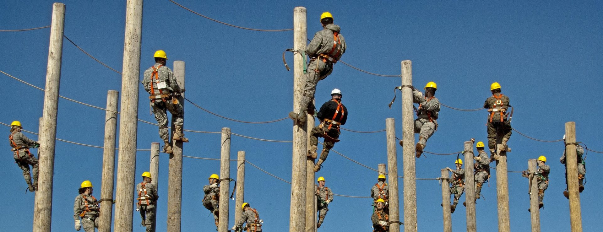 Several workers on the top of electric poles working
