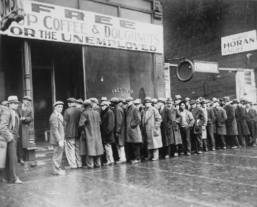 Photo shows a line of people in long coats and hats standing in line outside a building with a sign that states