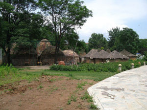 a cluster of thatched-roof circular buildings under trees, with a small garden in front of them