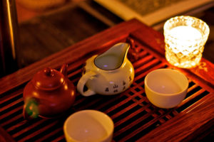 Two small teapots, two Chinese white teacups, and a votive candle sitting on a wooden tray