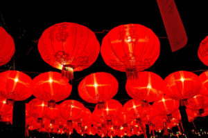 Strings of red round Chinese lanterns against a black night sky
