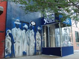 la entrada del Nuyorican Poets Cafe tiene un mural pintado dramático con personas vestidos en blanco contra un trasfondo azul