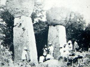 foto de dos piedras latte con hombres al lado: los pilares son al menos once o doce pies de altura, con las piedras redondas encima que añaden otros cuatro pies más