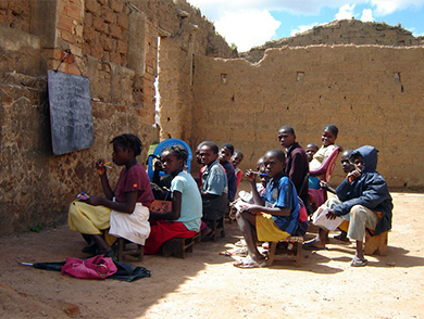 This is an image of children sitting in a ruined structure which serves as their outdoor