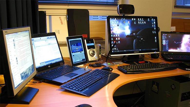 This image is a photograph of multiple laptop computers and other electronic devices.