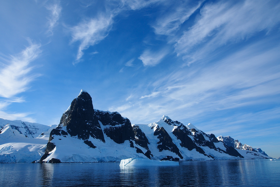 Picture of Antartica showing water, mountain, and iceberg peaks under a bright blue sky