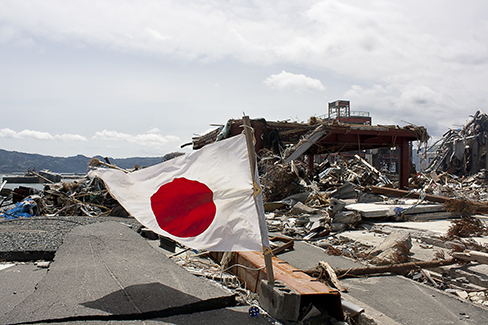 Photo of the aftermath of the earthquake in Japan with a focus on the Japanese flag.