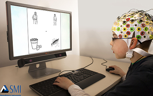 A photograph depicts a person looking at a computer screen and using the keyboard and mouse. The person wears a white cap covered in electrodes and wires.