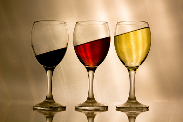 Three wine glasses on a flat surface with dark red, light red, and yellow liquid. The surface level of each liquid is at a tilt that would be impossible on an actual flat surface.