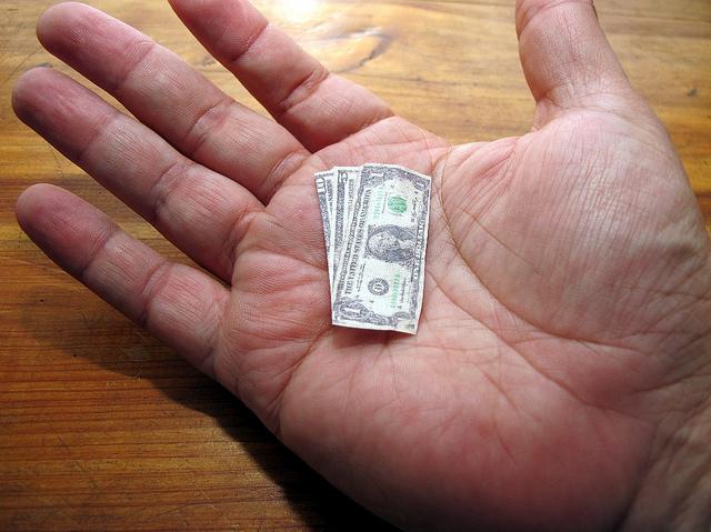 open palm holding miniature dollar bills