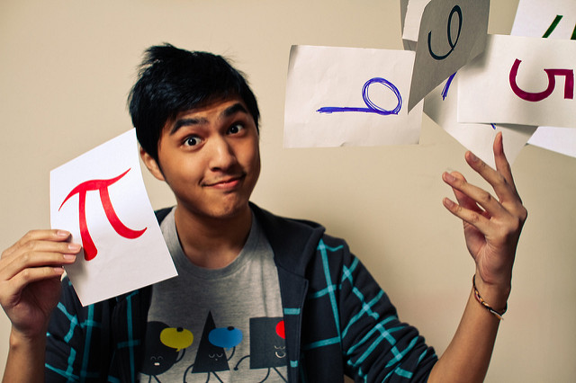 Young man holding a page with a red pi symbol in one hand, and tossing pages with numbers on them from the other hand