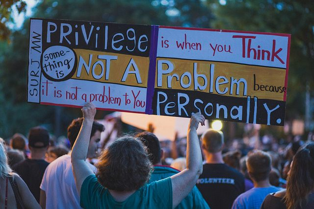 """A protest sign reads: """"Privilege is when you think something is not a problem because it is not a problem to you personally."""