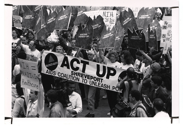 """Black and white photo of activists holding signs reading """"NIH=Nazis In Healthcare"""" and """"We're fired up."""""""
