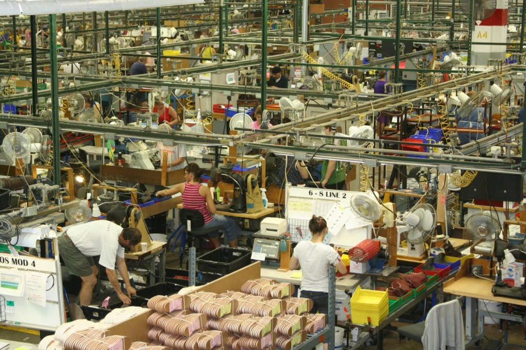 Photograph of factory workers for a shoe company working separately on individualized tasks.