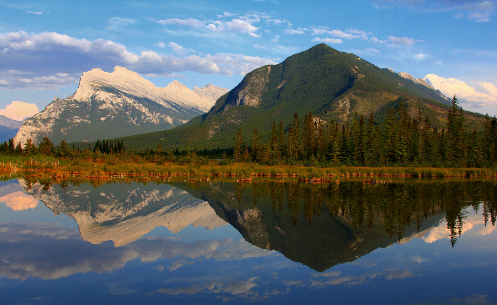 Photo of a clear lake with mountains in the distance reflected in the water. Blue sky, a few clouds.