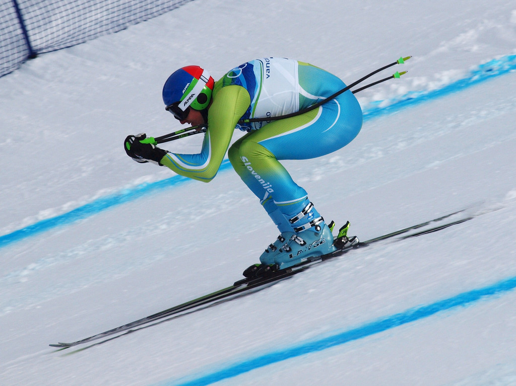 Skier in a tucked position, racing downhill.