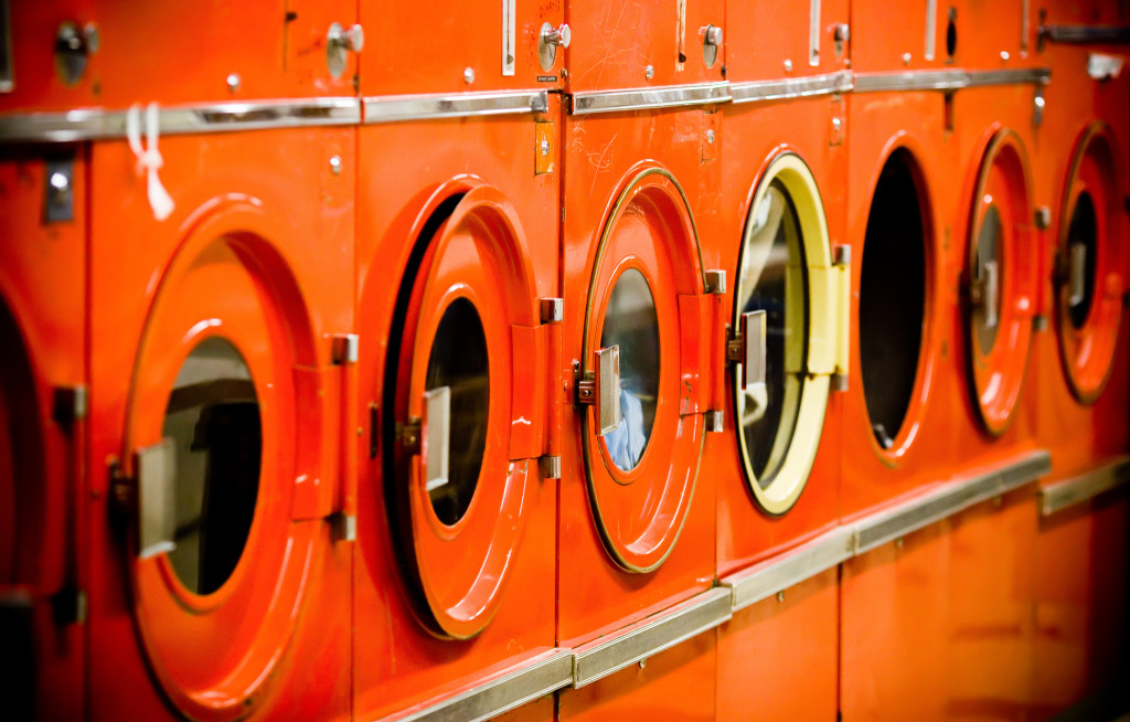 Photo of a row of orange coin-operated washing machines.